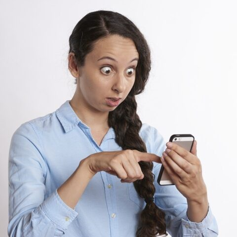 Woman staring at smartphone with shocked expression on her face